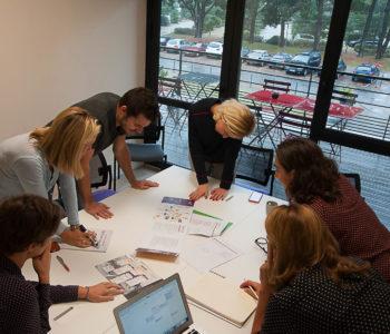 Équipe dans une salle de réunion autour table vue arbres nature travail team discussion bureaux à louer location domiciliation commerciale salle réunion Centre d'affaires lorient mer