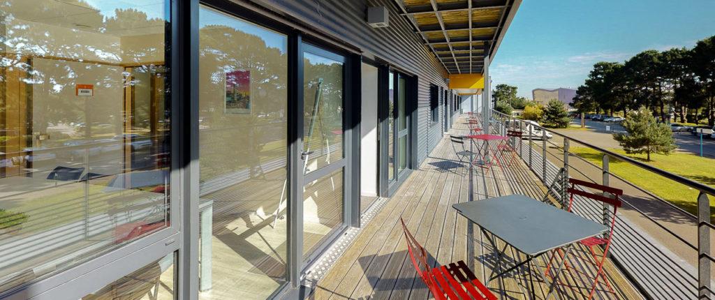 Vue terrasse table chaise pelouse nature arbres soleil mer bureaux centre d'affaires Lorient mer